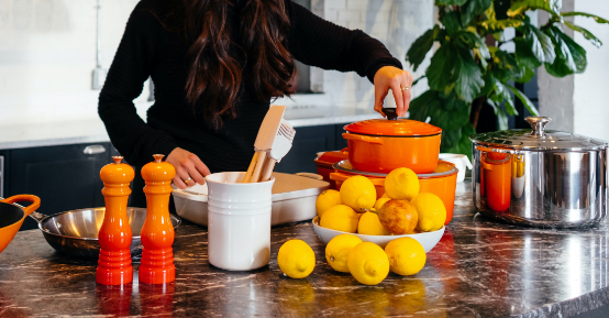 Person in kitchen with pots and pans and large bowl of citrus fruits.