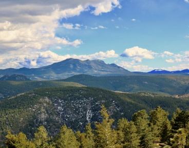 Colorado mountain view with tall peaks, green trees, and cloudy blue skies.