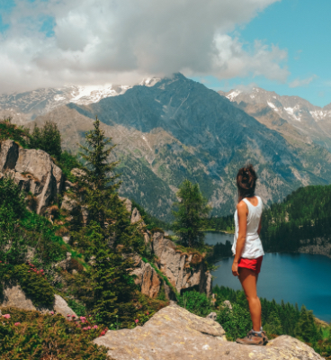 Person in tank top and shorts standing on rocks overlooking mountain valleys with lakes.